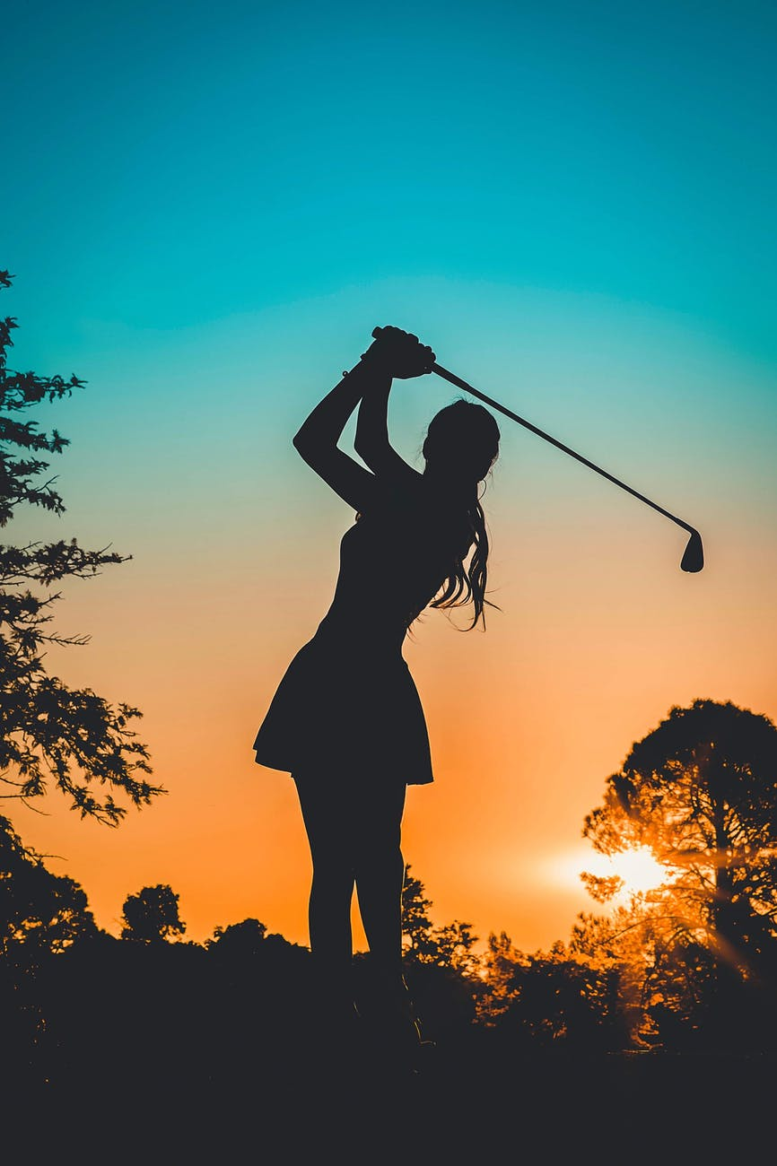 silhouette photo of a woman playing golf