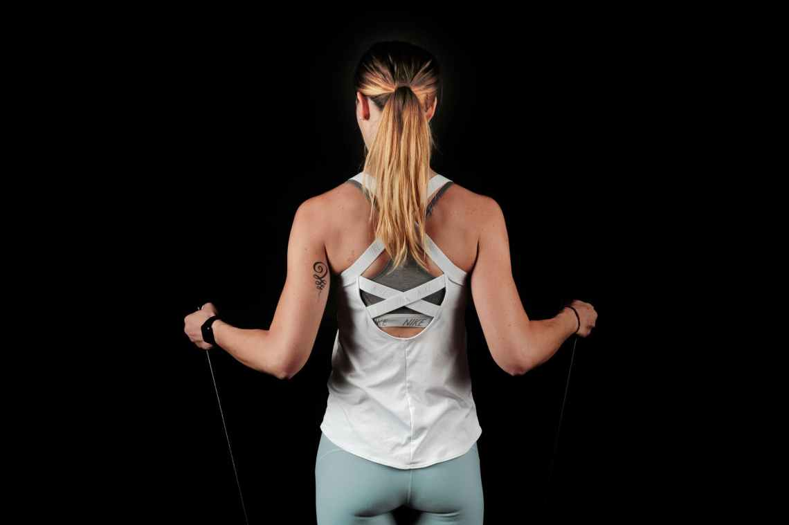 back view photo of woman pulling on resistance band with her arms while standing against black background