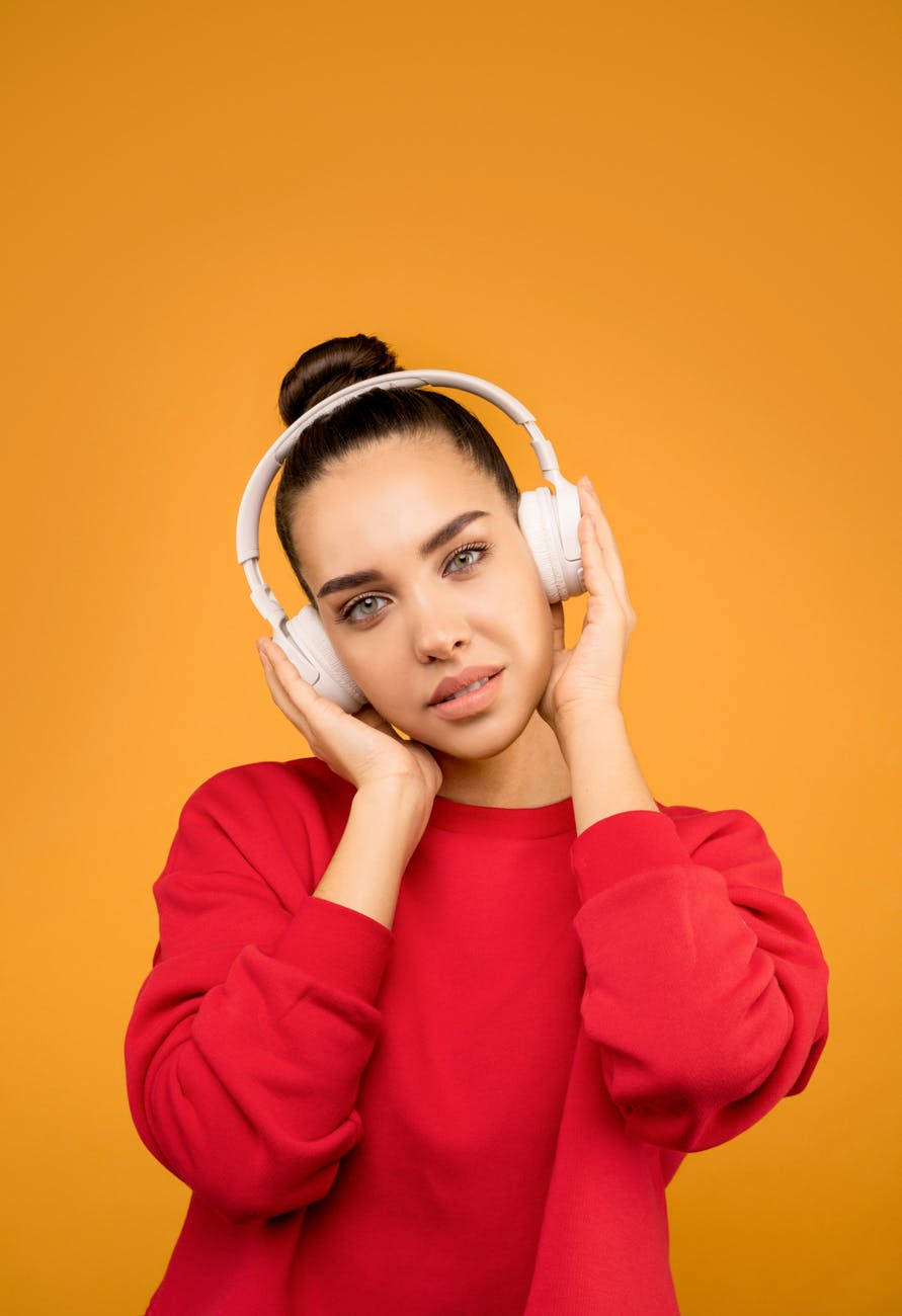 young woman wearing red long sleeves and white headphones
